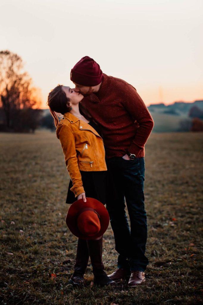 Outdoorshooting. Paarshooting. Paar küsst sich im Sonnenuntergang.